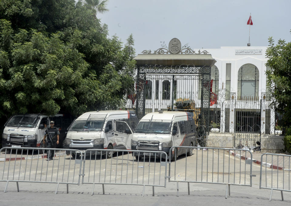FILE - In this July 27, 2021 file photo, police cars and a military armored personnel carrier block a side entrance of the Tunisian parliament in Tunis. Days of political turmoil in Tunisia over the economy and the coronavirus have left its allies in the Middle East, Europe and the United States watching to see if the fragile democracy will survive. (AP Photo/Hassene Dridi, File)