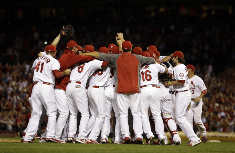 Members of the St. Louis Cardinals celebrate after the Cardinals' 7-0 win over the Chicago Cubs in a baseball game to clinch the NL Central title Friday, Sept. 27, 2013, in St. Louis. (AP Photo/Jeff Roberson)