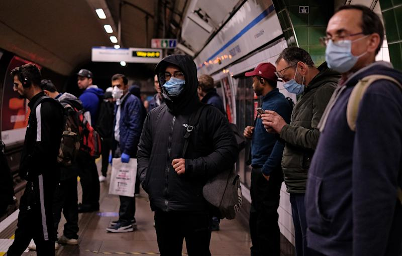 Commuters wearing PPE (personal protective equipment), including a face mask as a precautionary measure against COVID-19, travel in the morning rush hour on TfL (Transport for London) London underground Victoria Line trains from Finsbury Park towards central London on May 13, 2020, as people start to return to work after COVID-19 lockdown restrictions were eased. - Britain's economy shrank two percent in the first three months of the year, rocked by the fallout from the coronavirus pandemic, official data showed Wednesday, with analysts predicting even worse to come. Prime Minister Boris Johnson began this week to relax some of lockdown measures in order to help the economy, despite the rising death toll, but he has also stressed that great caution is needed. (Photo by Isabel INFANTES / AFP) (Photo by ISABEL INFANTES/AFP via Getty Images)