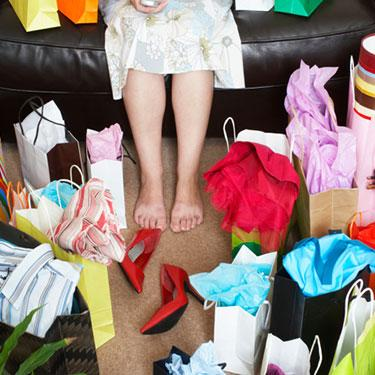 Woman-sitting-on-sofa-surrounded-with-shopping-bags_web