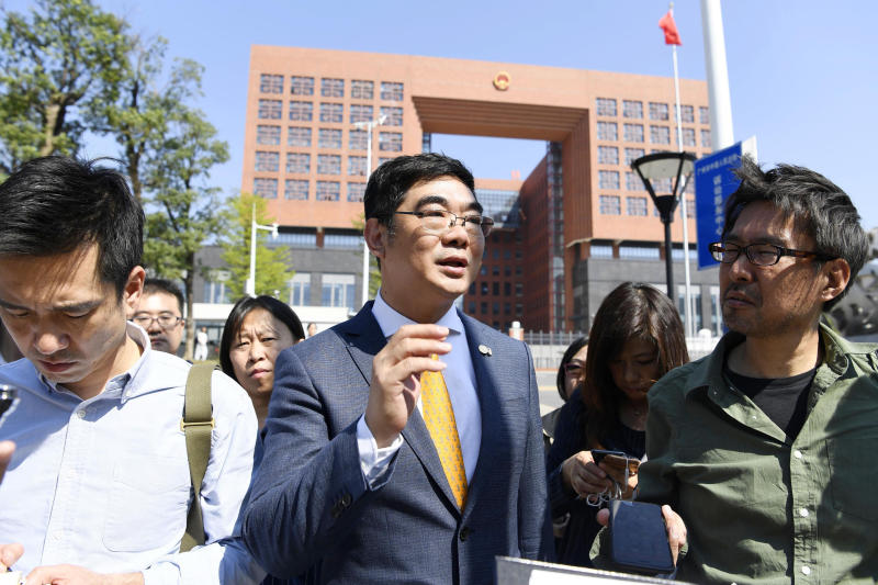 Chen Weixiong, center, lawyer of former Japanese politician Takuma Sakuragi, leaves the Guangzhou City First Intermediate Court, seen in the background, after a sentencing in Guangzhou, southern China Friday, Nov. 8, 2019. The court on Friday sentenced Sakuragi to life in prison in a 5-year-old drug trafficking case. (Naohiko Hatta/Kyodo News via AP)