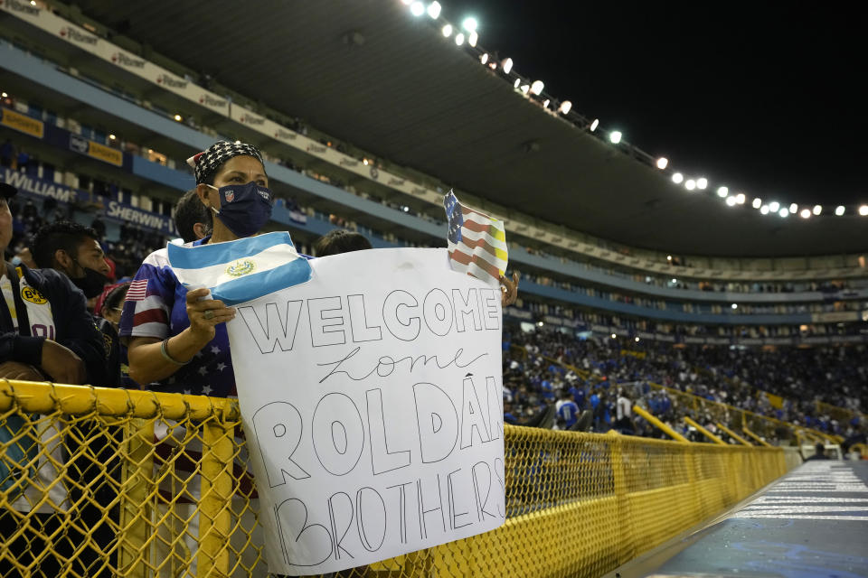 A fan holds up a sign before a qualifying soccer match between El Salvador and United States for the FIFA World Cup Qatar 2022 at Cuscatlan stadium in San Salvador, El Salvador, Thursday, Sept. 2, 2021. (AP Photo/Moises Castillo)
