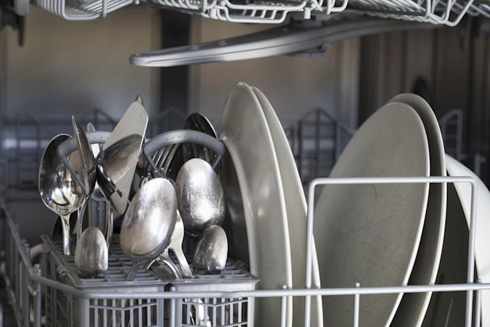 Pour ½ cup of white vinegar into the detergent cups and run the empty machine for a complete cycle.