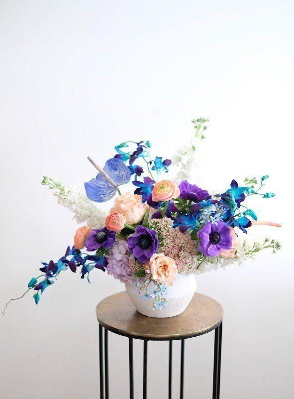 """<p>This Easter, experiment with unexpected and quirky flower combinations. Take inspiration from this vibrant arrangement from <a href=""""https://www.diosablooms.com/flowers/p/amansinaya"""" rel=""""nofollow noopener"""" target=""""_blank"""" data-ylk=""""slk:Diosa Blooms"""" class=""""link rapid-noclick-resp"""">Diosa Blooms</a>, which includes a mix of coral roses, blue orchids and anthuriums, and seasonal purple flowers. </p><p><strong><em>Raawii Alev Earthenware Vase, $55,</em></strong> <a class=""""link rapid-noclick-resp"""" href=""""https://go.redirectingat.com?id=74968X1596630&url=https%3A%2F%2Fwww.matchesfashion.com%2Fus%2Fproducts%2FRaawii-Alev-earthenware-vase-1388140&sref=https%3A%2F%2Fwww.housebeautiful.com%2Fentertaining%2Fflower-arrangements%2Fg19409803%2Feaster-flower-arrangements%2F"""" rel=""""nofollow noopener"""" target=""""_blank"""" data-ylk=""""slk:BUY NOW"""">BUY NOW</a></p>"""