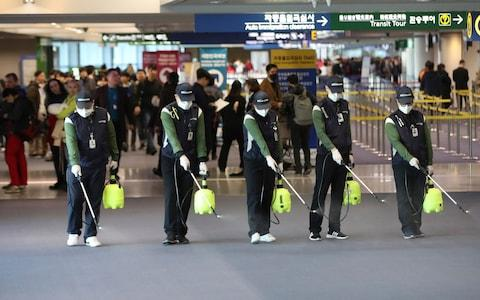 Workers spray antiseptic solution on the arrival lobby amid rising public concerns over the possible spread of a new coronavirus at Incheon International Airport in Incheon, South Korea - Credit: Suh Myung-geon/Yonhap