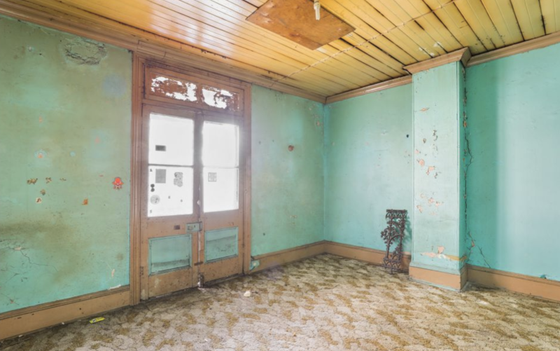 The inside of a Waterloo home in Sydney is seen with paint coming off the walls.