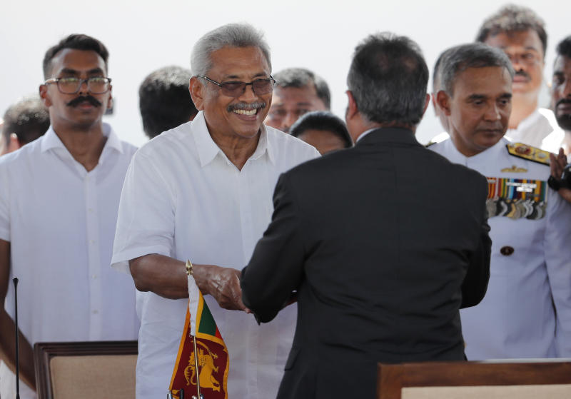 Sri Lanka's newly elected president Gotabaya Rajapaksa, second left, greets as he takes the oath of office in front of chief justice Jayantha Jayasuriya, back to camera as his son Manoj, left, watches during the swearing in ceremony held at the 140 B.C Ruwanweli Seya Buddhist temple in ancient kingdom of Anuradhapura in north central Sri Lanka Monday, Nov. 18, 2019. The former defense official credited with ending a long civil war was Monday sworn in as Sri Lanka's seventh president after comfortably winning last Saturday's presidential election. (AP Photo/Eranga Jayawardena)