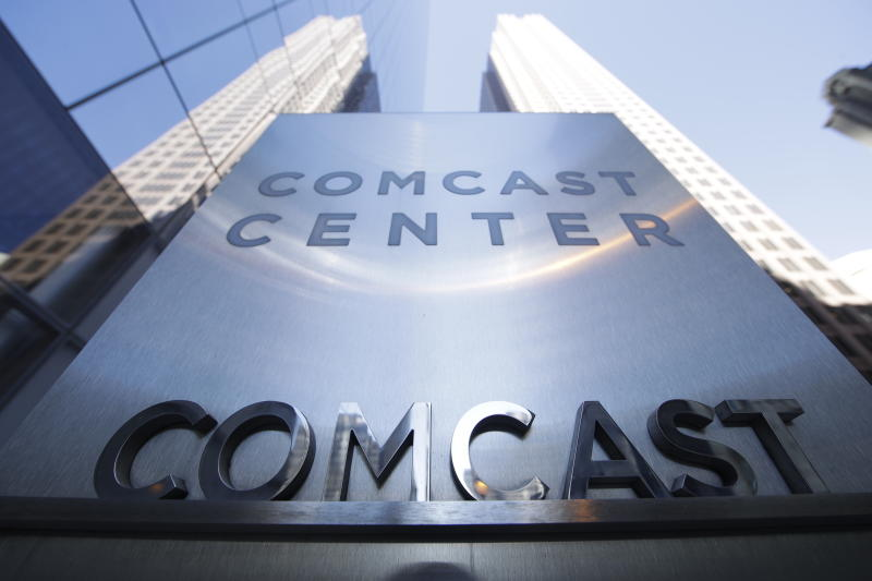 FILE - This March 29, 2017, file photo shows a sign outside the Comcast Center in Philadelphia. Comcast says it's dropping out of the bidding war for Twenty-First Century Fox's entertainment business, instead focusing on its bid for Sky. (AP Photo/Matt Rourke, File)