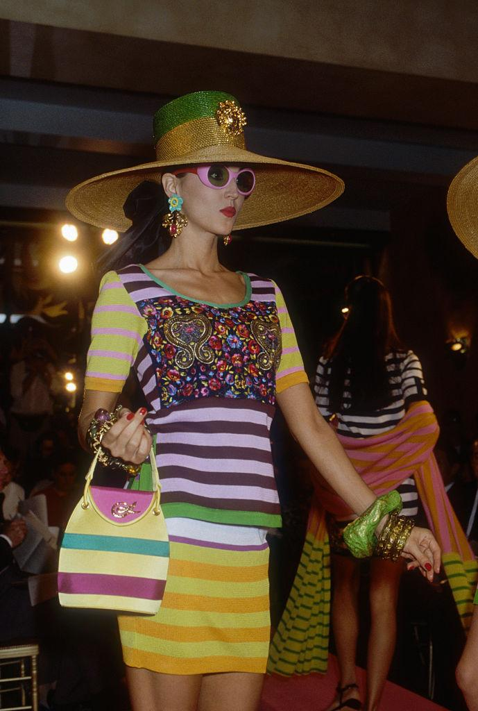 Japanese designer Kenzo Takada shows his women's 1991 spring-summer ready-to-wear line in Paris. The model is wearing a striped skirt and top with a large sun hat. (Photo by Pierre Vauthey/Sygma/Sygma via Getty Images)