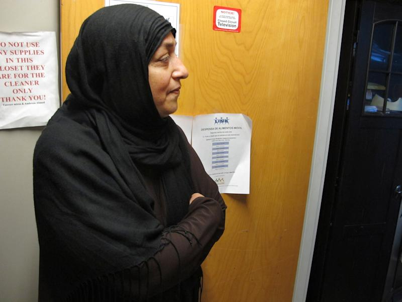 """In this Monday, Jan. 27, 2014 photo, Tanveer Mirza stands in the FAITH Social Services offices in Herndon, Va. Mirza emigrated from Pakistan 37 years earlier. In 1999 her mosque started this effort to assist refugees from the civil war in Bosnia who were being resettled in Northern Virginia. They soon realized that, even amid relative wealth, there were many who needed assistance, including many non-Muslims. """"You don't think there are people in need, but there are a lot of them,"""" says Mirza, the organization's president. """"You don't see them."""" (AP Photo/Adam Geller)"""