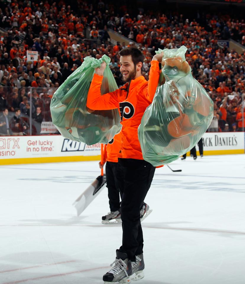 PHILADELPHIA, PA - APRIL 29: An ice crew member removes hats from the ice following a hattrick by Wayne Simmonds #17 of the Philadelphia Flyers against the New York Rangers in Game Six of the First Round of the 2014 NHL Stanley Cup Playoffs at the Wells Fargo Center on April 29, 2014 in Philadelphia, Pennsylvania. (Photo by Bruce Bennett/Getty Images)