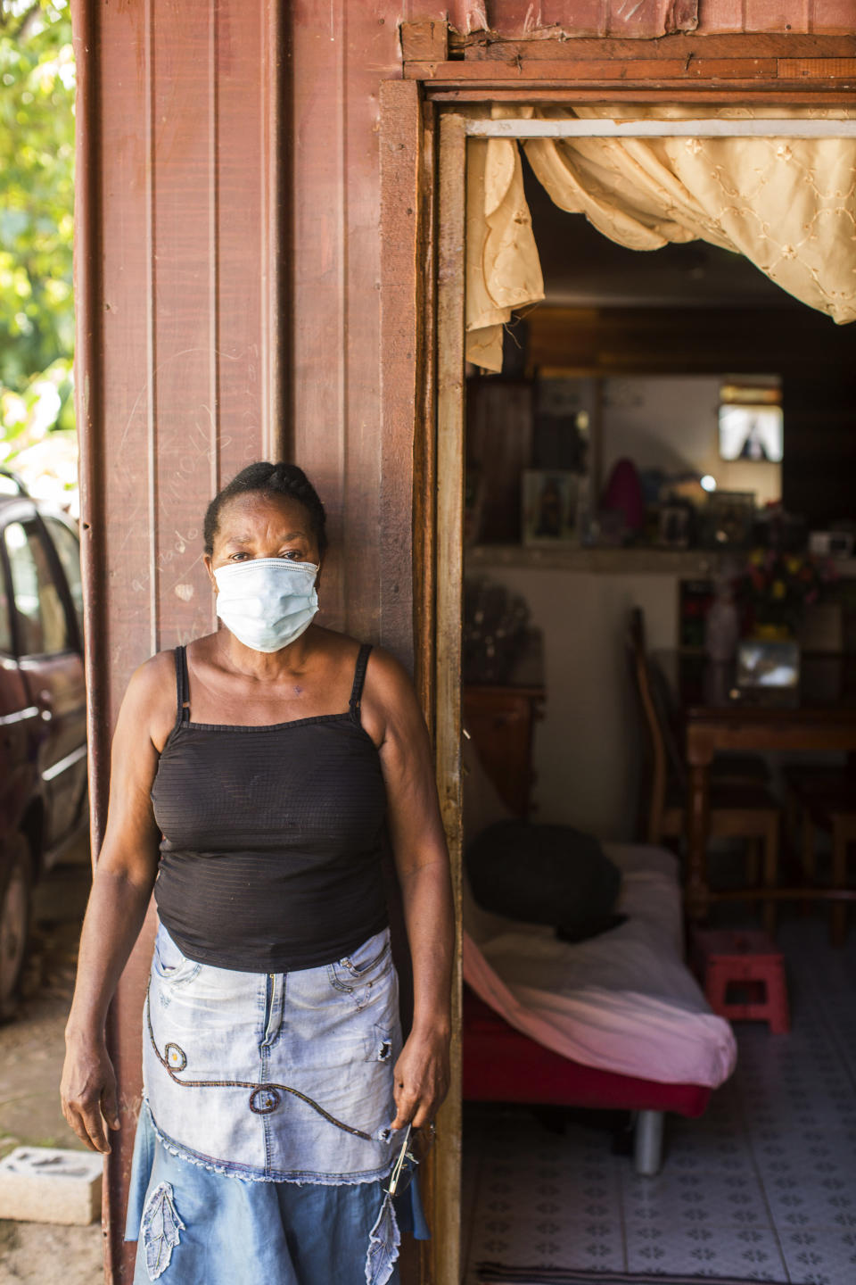 A woman from Haiti poses in front of her home in the slum district of Mont Baduel, in Cayenne, French Guiana, Friday, July 10, 2020. France's most worrisome virus hotspot is in fact on the border with Brazil - in French Guiana, a former colony where health care is scarce and poverty is rampant. The pandemic is exposing deep economic and racial inequality in French Guiana that residents say the mainland has long chosen to ignore. (AP Photo/Pierre Olivier Jay)
