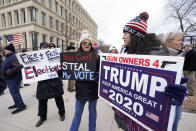 Protesters hold signs outside the Richard H. Austin state office building during a rally in Lansing, Mich., Saturday, Nov. 14, 2020. Michigan's elections board is meeting to certify the state's presidential election results. (AP Photo/Paul Sancya)