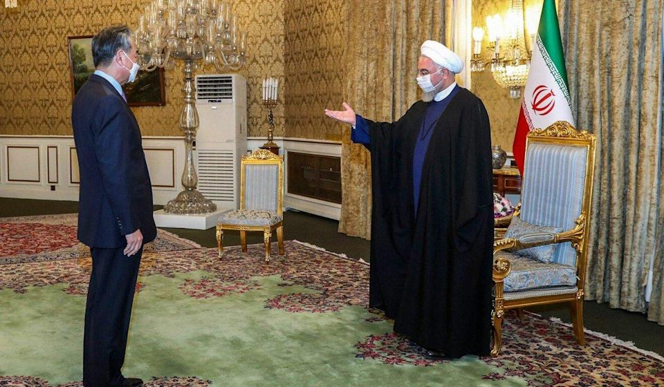 President Hassan Rouhani greets Chinese Foreign Minister Wang Yi at the presidential palace. Photo: AFP