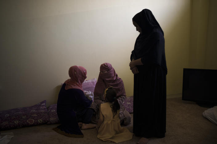 Mujdha, left, holds her 13-days-old daughter as she talks to Razia and her daughter Alia inside the women's section of the Pul-e-Charkhi prison in Kabul, Afghanistan, Thursday, Sept. 23, 2021. When the Taliban took control of a northern Afghan city of Pul-e-Kumri the operator of the only women's shelter ran away, abandoning 20 women in it. When the Taliban arrived at the shelter the women were given two choices: Return to their abusive families, or go with the Taliban, With nowhere to put the women, the Taliban took them to the abandoned women's section of Afghanistan's notorious Pul-e-Charkhi prison. (AP Photo/Felipe Dana)