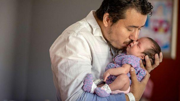 PHOTO: Juan Duran-Gutierrez kisses his newborn baby girl Andrea for the first time in his home after bringing her home from North Memorial Hospital, Aug. 5, 2020, in Brooklyn Center, Minn. (Elizabeth Flores/Minneapolis Star Tribune/TNS via Newscom)