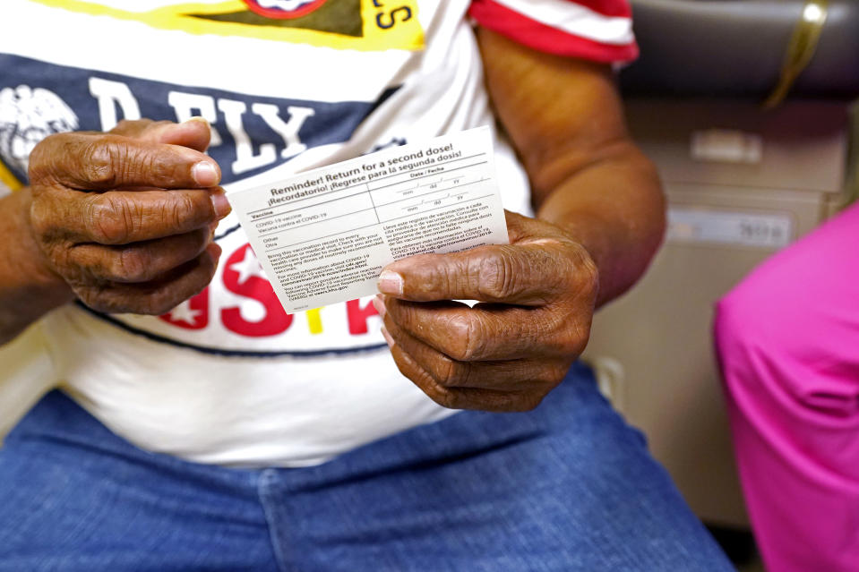 Wilbert Marshall, 71, looks at his shot card after receiving the COVID-19 vaccine at the Aaron E. Henry Community Health Service Center in Clarksdale, Miss., Wednesday, April 7, 2021. Marshall was among a group of seniors from the Rev. S.L.A. Jones Activity Center for the Elderly who received their vaccinations. More Black Americans say they are open to taking the coronavirus vaccine amid campaigns to overcome a shared historical distrust of science and government. (AP Photo/Rogelio V. Solis)