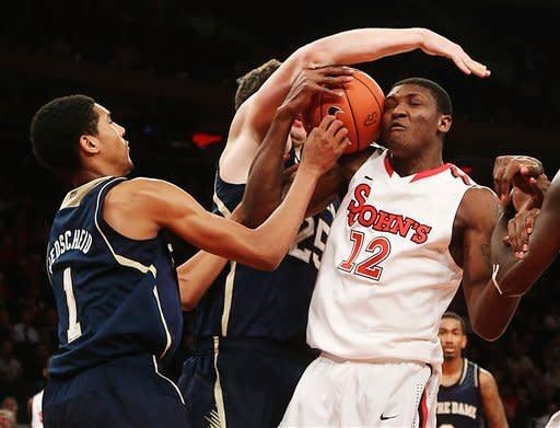 St. John's Chris Obekpa (12) fights for a rebound against Notre Dame's Cameron Biedscheid (1) and Tom Knight during the second half of their NCAA college basketball game, Tuesday, Jan. 15, 2013, at Madison Square Garden in New York. St. John's won 67-63. (AP Photo/Mary Altaffer)