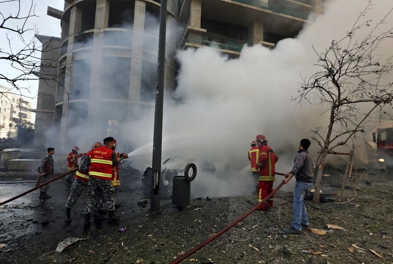 Lebanese firefighters extinguish burned vehicles at the scene of an explosion in Beirut, Lebanon, Friday, Dec. 27, 2013. A strong explosion has shaken the Lebanese capital, sending black smoke billowing from the center of Beirut. The blast went off a few hundred meters (yards) from the government headquarters and parliament building. (AP Photo/Bilal Hussein)