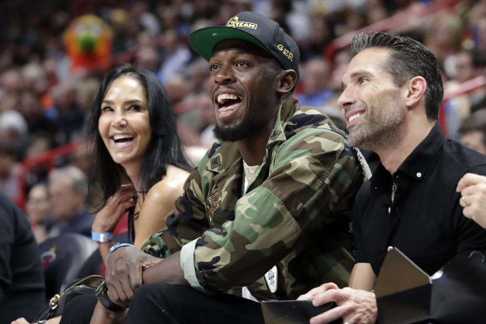 FILE - In this Dec. 13, 2019, file photo, Usain Bolt watches the first half of an NBA basketball game between the Miami Heat and Los Angeles Lakers in Miami. The retired sprinting great recently had twins, which is keeping him plenty busy. He thinks one of the favorites to win the 100 meters at the Tokyo Games is American Trayvon Bromell. (AP Photo/Lynne Sladky, File)