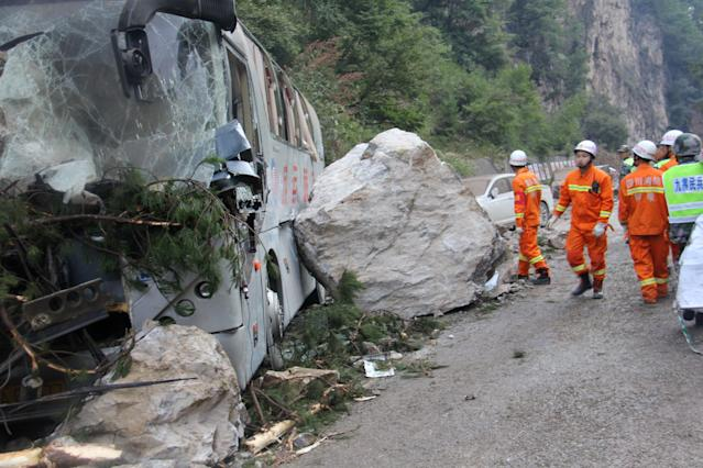 <p>Chinese paramilitary police are seen beside a wrecked tour bus as they conduct rescue operations in Jiuzhaigou in China's southwestern Sichuan province on Aug. 9, 2017, after an 6.5-magnitude earthquake struck the province late on Aug. 8. (Photo: STR/AFP/Getty Images) </p>