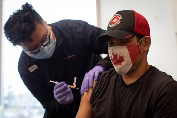 Team Canada wheelchair rugby player Travis Murao, 38, receives his second dose of the Pfizer-BioNTech COVID-19 vaccine ahead of the Paralympics. (Evan Mitsui/CBC - image credit)
