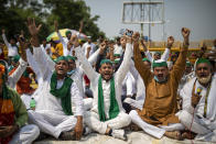 Indian farmers shout slogans as they block a highway during a protest in Noida, India, Friday, Sept. 25, 2020. Hundreds of Indian farmers took to the streets on Friday protesting new laws that the government says will boost growth in the farming sector through private investments, but they fear these are likely to be exploited by private players for buying their crops cheaply. (AP Photo/Altaf Qadri)