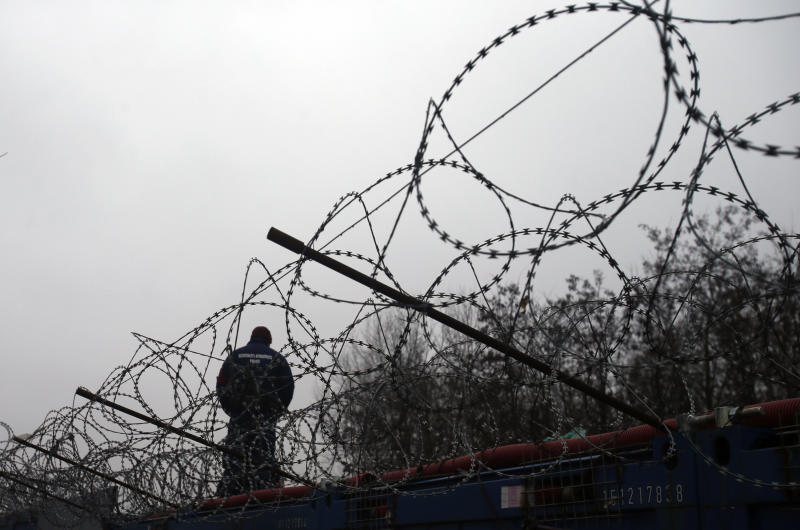 FILE - In this file photo dated Wednesday, Feb. 8, 2017, a Hungarian police officer stands guard at Serbia's border with Hungary near a makeshift camp for migrants in Horgos, Serbia. The European Court of Justice on Wednesday Sept.6, 2017, rejected efforts by Hungary and Slovakia to stay out of a European Union scheme to relocate refugees. (AP Photo/Darko Vojinovic, FILE)