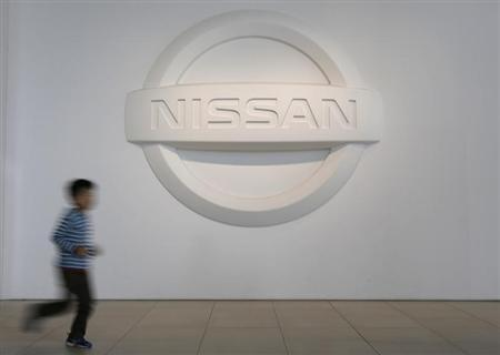 A visitor runs past the logo of Nissan Motor Co at the company's showroom in Yokohama
