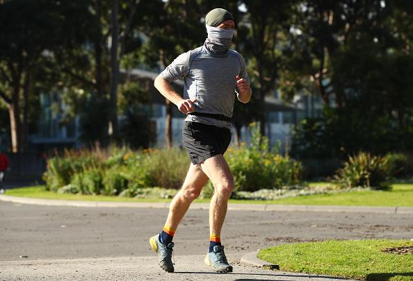 A man with a face covering is seen running through Carlton Gardens in Melbourne, Australia.