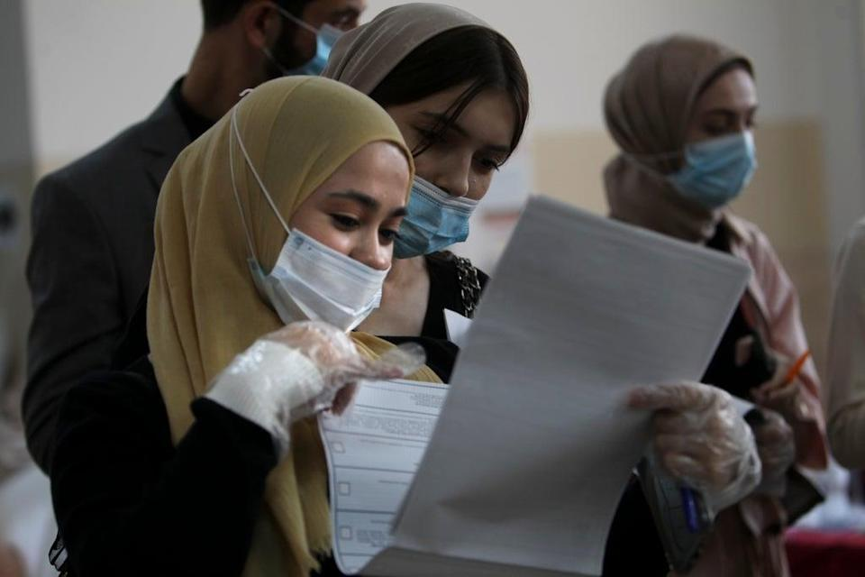 Chechen women wait to fill in their ballots at a polling station during the elections in Grozny, Russia (AP)