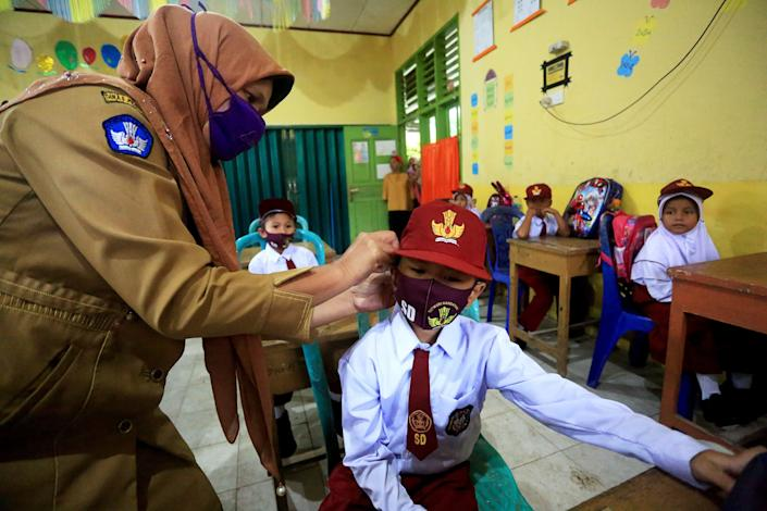 A teacher helps an elementary school student with a face mask on the first day of school in the 2020-2021 academic year in Pesisir Selatan region, West Sumatra, Indonesia, on July 13. Students in Indonesia went back to schools in low-risk areas under tight health protocols.