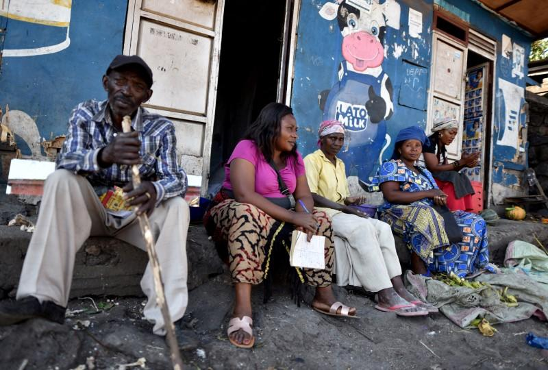 Traders sit near a deserted crossing point between the Democratic Republic of Congo and Rwanda amid concerns about the spread of coronavirus disease (COVID-19), at the Petite Barriere in Goma