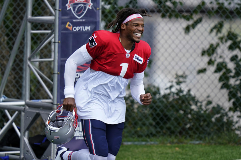 New England Patriots quarterback Cam Newton smiles as he steps on the field at the start of practice. (AP Photo/Steven Senne, Pool)