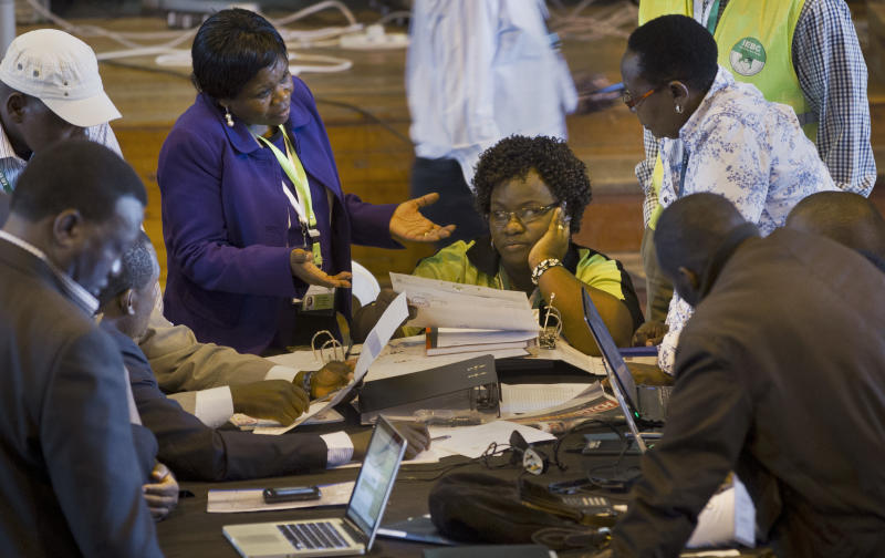 FILE - In this Wednesday, March 6, 2013 file photo, official representatives of the various political parties and electoral workers discuss while reviewing newly received results, at the National Tallying Center in Nairobi, Kenya. Vote totals for Kenya's president-elect mysteriously increased between the time the ballot numbers were announced at some remote polling centers and when they reached the national tallying center in the capital, a lawyer for a civil society group told the country's Supreme Court on Wednesday, March 27, 2013. (AP Photo/Ben Curtis, File)