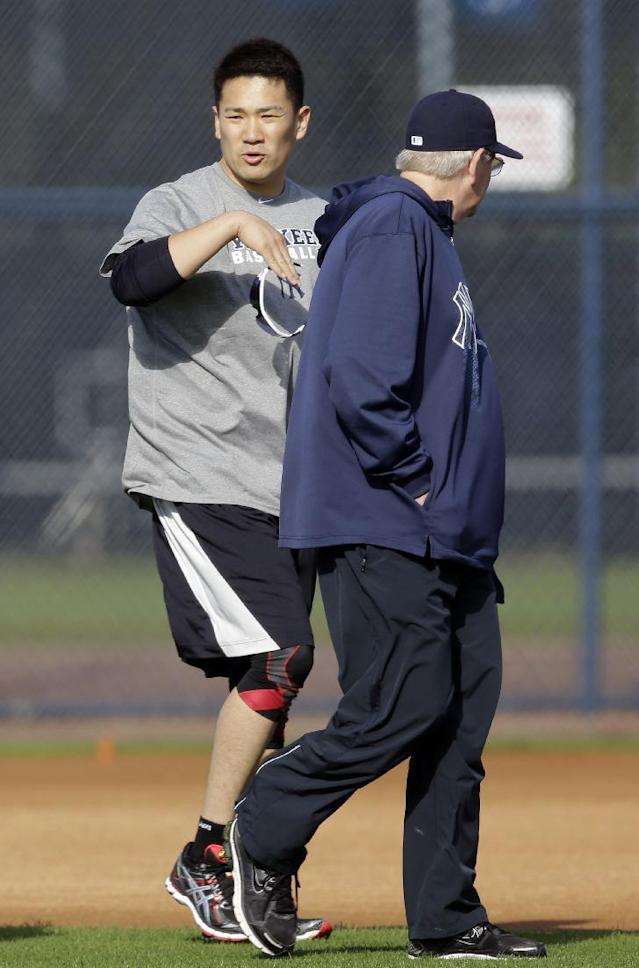 New York Yankees pitcher Masahiro Tanaka, left, of Japan, gestures as he talks to pitching coach Larry Rothschild during practice at the Yankees' minor league facility Thursday, Feb. 13, 2014, in Tampa, Fla. (AP Photo/Chris O'Meara)