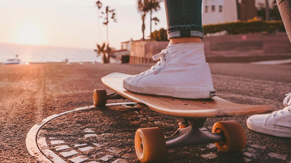 woman on skateboard riding off into the sunset