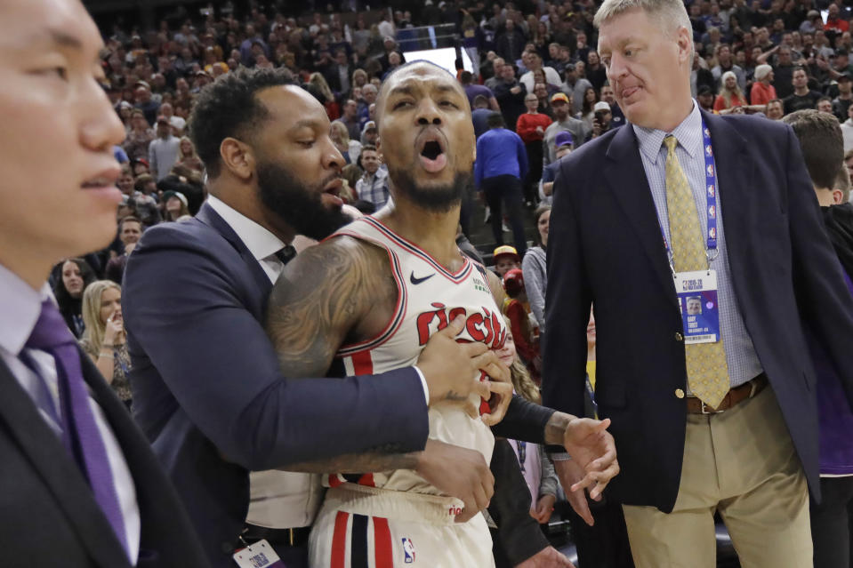 Portland Trail Blazers guard Damian Lillard (0) is held back following the team's NBA basketball game against the Utah Jazz on Friday, Feb. 7, 2020, in Salt Lake City. The Jazz won 117-114. (AP Photo/Rick Bowmer)