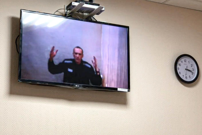 Russian opposition leader Alexei Navalny gestures speaking in a video link from a prison during a court session in Petushki, Vladimir region, about 120 kilometers (75 miles) east of Moscow, Russia, Monday, May 31, 2021. Imprisoned Russian opposition leader Alexei Navalny has asked a court to halt the hourly nighttime checks he has been subjected to in his penal colony. Speaking Monday in a video link from prison, Navalny charged that he has done nothing that would warrant the authorities' decision to designate him as a flight risk that has resulted in checks. (TV Rain via AP)