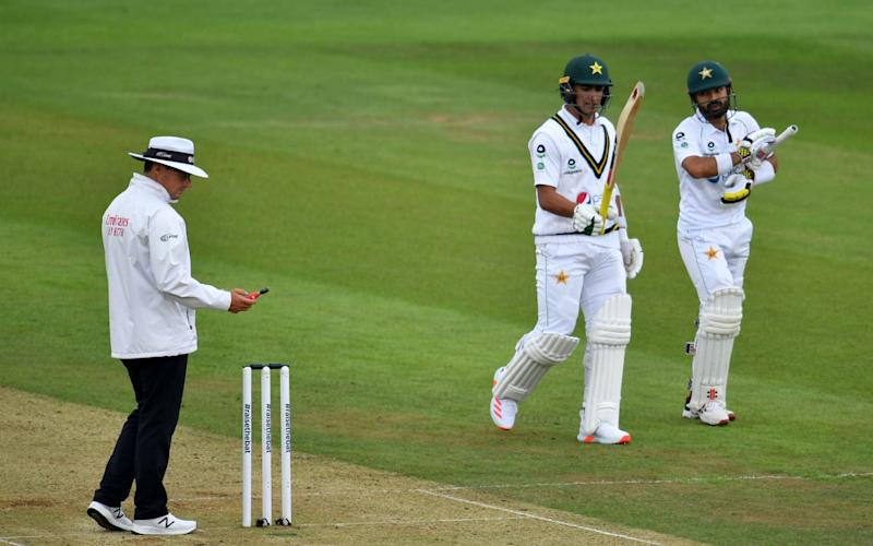 The umpire takes a light-reading as the batsmen walk back to the dressing room as play is delayed for bad light on the second day of the second Test cricket match between England and Pakistan at the Ageas Bowl in Southampton, southwest England on August 14, 2020.  - AFP