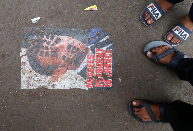 People stand next to a defaced poster of France's President Emmanuel Macron on a road as a mark of a protest, in Mumbai