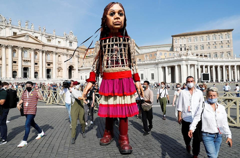 Little Amal, a 3.5 metre tall puppet of a young Syrian refugee girl, is greeted in Vatican as she travels across Europe from Turkey to Britain as part of an 8,000 kilometre walk to raise awareness for the plight of young refugees, Vatican, September 10, 2021. REUTERS/Remo Casilli