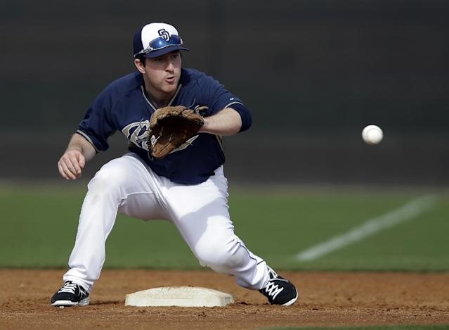 San Diego Padres' Jedd Gyorko reaches out for a throw from the catcher as infielders and pitchers participate in pick-off drills during spring training baseball practice, Friday, Feb. 21, 2014, in Peoria, Ariz. (AP Photo/Tony Gutierrez)