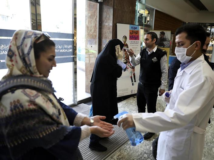 <p>Temperatures are checked and hands disinfected at a shopping centre in Tehran</p> (AP)