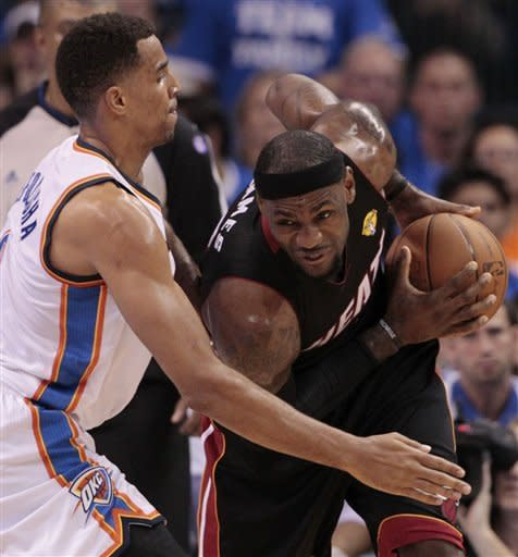 Miami Heat small forward LeBron James is guarded by Oklahoma City Thunder shooting guard Thabo Sefolosha (2) of Switzerland during the first half at Game 2 of the NBA finals basketball series, Thursday, June 14, 2012, in Oklahoma City. (AP Photo/Jeff Roberson)
