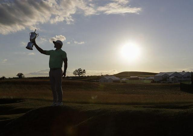 Brooks Koepka holds up the U.S. Open championship trophy as the sun falls on Erin Hills. (AP)