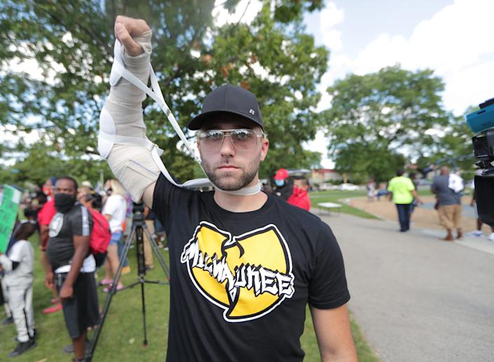 Gaige Grosskreutz, 26, of West Allis, who was shot in the arm during the Kenosha protests, holds up his arm before the march by a group supporting The Peoples Revolution from Johnsons Park on West Fond du Lac Avenue through the streets of Milwaukee on Sept. 5, 2020.