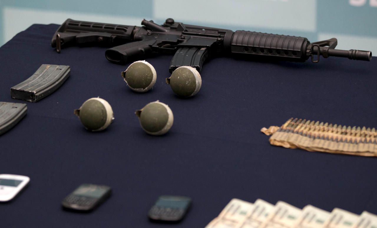 """Confiscated money, grenades, and guns are displayed during the media presentation of the alleged leader of a faction of the hyper-violent Zetas cartel, Ivan Velazquez Caballero, known as """"El Taliban,"""" at the Mexican Navy's Center for Advanced Naval Studies in Mexico City,Thursday, Sept. 27, 2012. Velazquez Caballero allegedly has been fighting a bloody internal battle with top Zetas' leader Miguel Angel Trevino Morales, and officials have said the split was behind a recent surge in massacres and shootouts, particularly in northern Mexico. (AP Photo/Eduardo Verdugo)"""