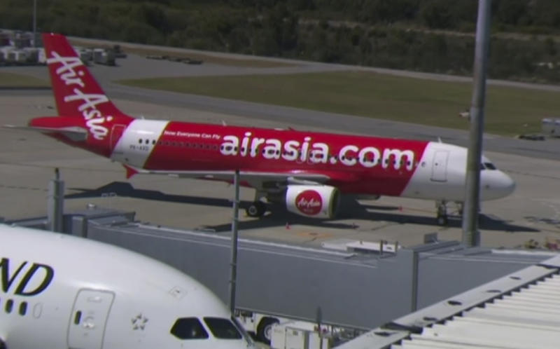 This Sunday, Oct. 15, 2017 image made from video shows an AirAsia plane at an airport in Perth, Australia. Passengers on the Indonesia AirAsia flight from Australia to the holiday island of Bali described a panicked flight crew announcing an emergency and oxygen masks dropping from the ceiling after their airliner lost cabin air pressure and rapidly descended. (Channel 9 via AP)