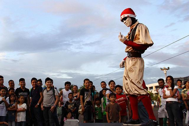 A mime artist performs at SM by the Bay SM Mall of Asia in Pasay City. Four days before Christmas, people go to malls and amusement parks with their family and friends to spend leisure time. The Philippines a predominantly catholic country has a longest Christmas celebration which starts on the month of September and ends on December. (Marlo Cueto/NPPA Images)